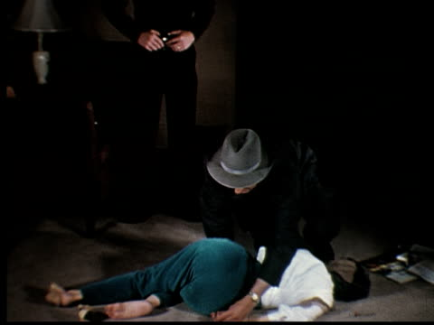 1965 film montage ms tu woman lying dead on the floor / ms detective and police officer kneeling beside corpse and talking/ ms police officer leaving as another detective arrives - dead person stock videos & royalty-free footage