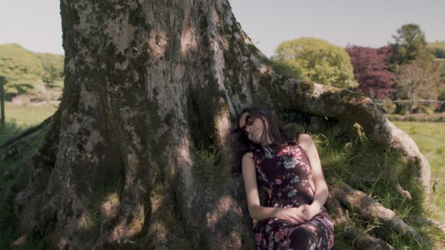 Woman lying down next to tree in summer, enjoying sun