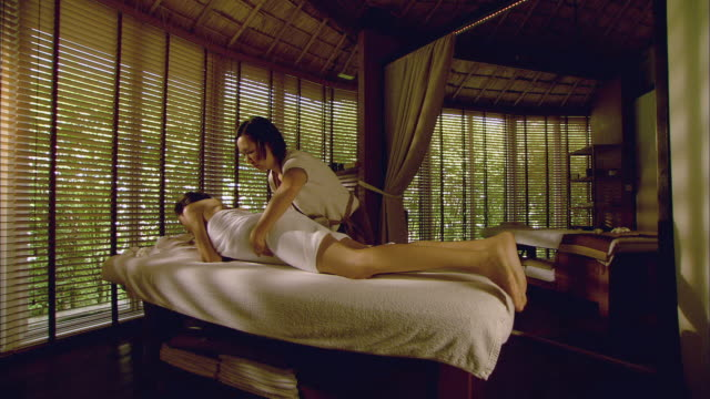 WS Woman lying down on massage table and massage therapist adjusting her towel / Hua Hin, Thailand