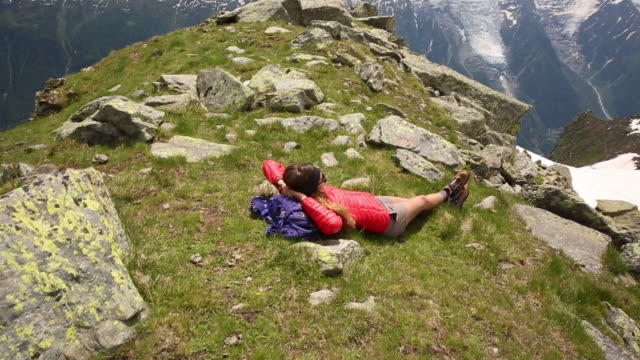 a woman lying down to relax on top of peak while hiking the french alps. - woman hands behind head stock videos & royalty-free footage