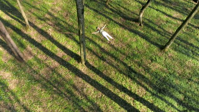 aerial frau liegt in einem wald - liegen stock-videos und b-roll-filmmaterial