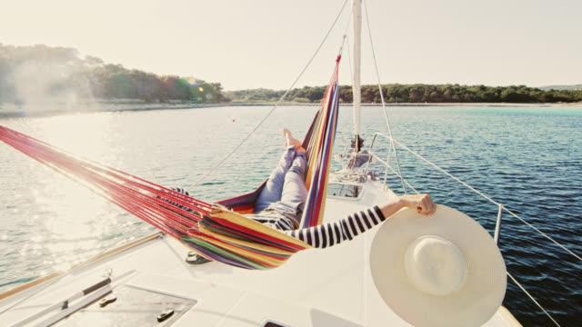 ws-frau liegen in der hängematte auf einem segelboot - erfrischung stock-videos und b-roll-filmmaterial