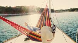 SLO MO Woman lying in a hammock on a sailboat