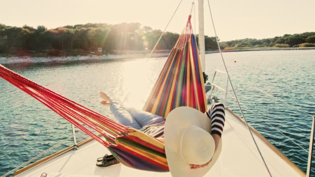 slo mo woman lying in a hammock on a sailboat - cappello video stock e b–roll