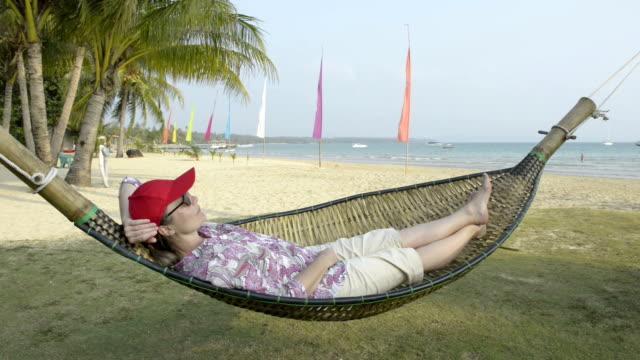 a woman lying in a hammock on sandy beach - gulf of thailand stock videos & royalty-free footage