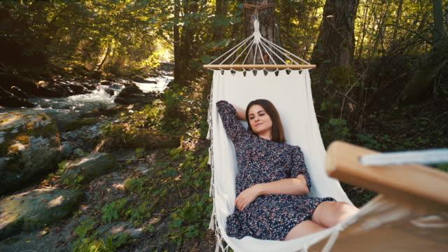 vídeos de stock, filmes e b-roll de mulher deitada numa cama de rede. - rede de dormir