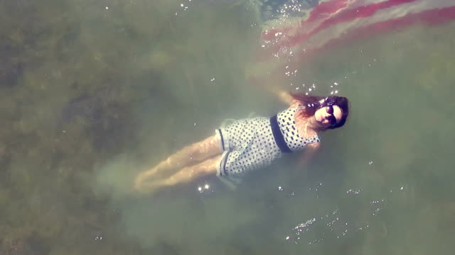 woman lying in a lake with the us flag - lying on back stock videos and b-roll footage