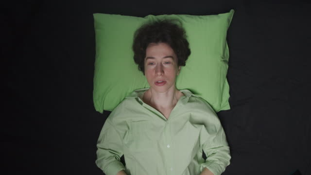 woman lying in bed and breathing deeply - lying on back stock videos & royalty-free footage