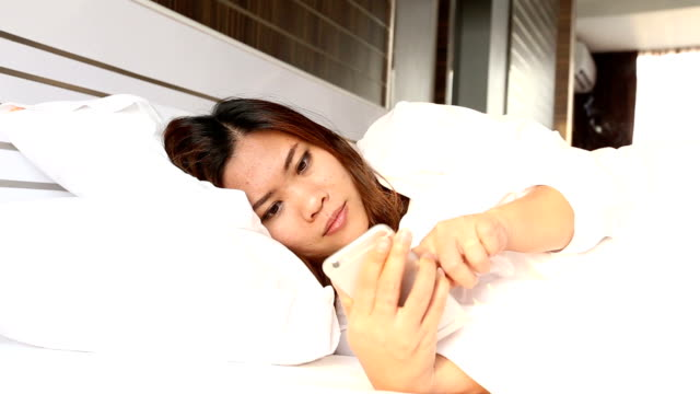 Woman lying  in bed checking social apps with smartphone and panic surprise face expression