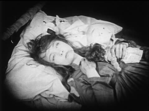 vídeos de stock e filmes b-roll de b/w 1919 woman lying in bed forcing lips to smile dies - 1919