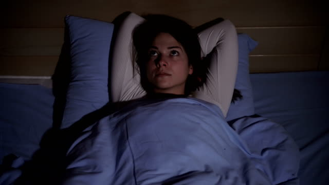 woman lying in bed suffering from insomnia - sleeping stock videos & royalty-free footage