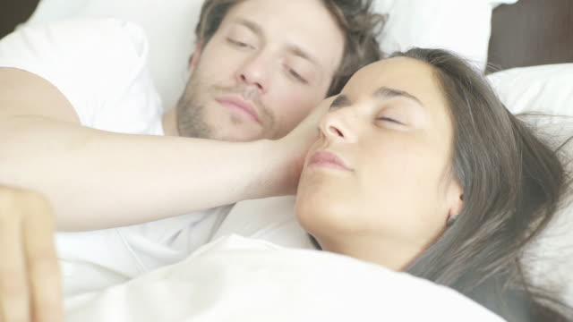 woman lying in bed taking temperature with thermometer - auf dem rücken liegen stock-videos und b-roll-filmmaterial