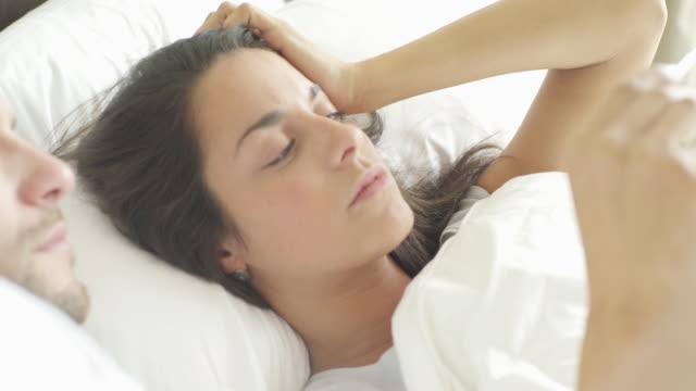 woman lying in bed taking temperature with thermometer - auf dem rücken liegen stock-videos und b-roll-filmmaterial