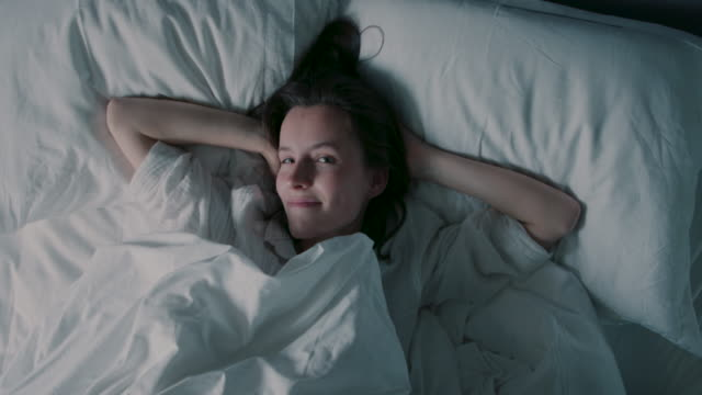 vídeos de stock e filmes b-roll de woman lying in bed, waking up, rubbing eyes - cama