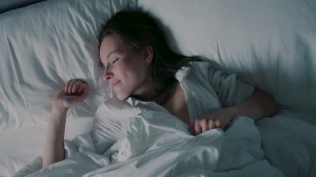 vídeos de stock e filmes b-roll de woman lying in bed, waking up - one woman only