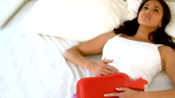 Woman lying in bed with cramps