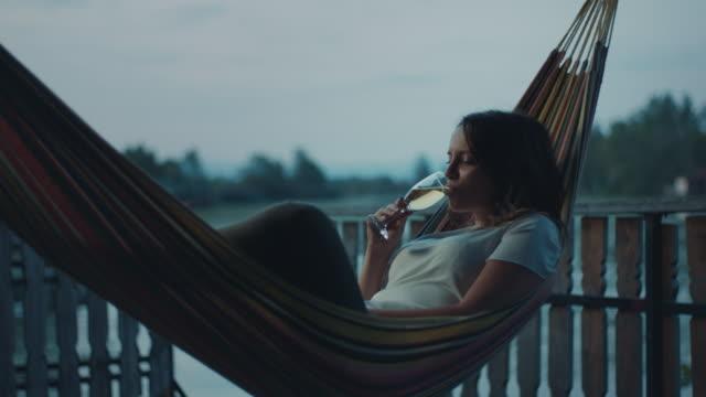 ハンモックに横たわり、シャンパンを飲む女性 - シャンパン点の映像素材/bロール