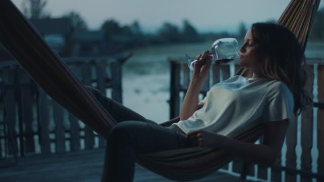 frau liegt in hängematte und trinkt wein - veranda stock-videos und b-roll-filmmaterial