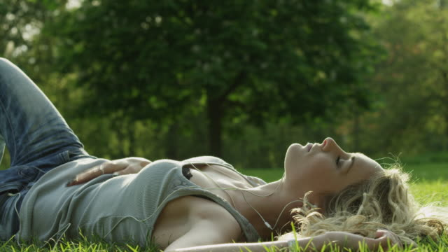 ms woman lying in park listening to music / london, uk - sdraiato video stock e b–roll
