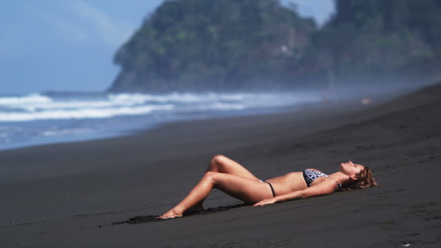 woman lying on a black sand beach in a bikini - swimwear stock videos and b-roll footage