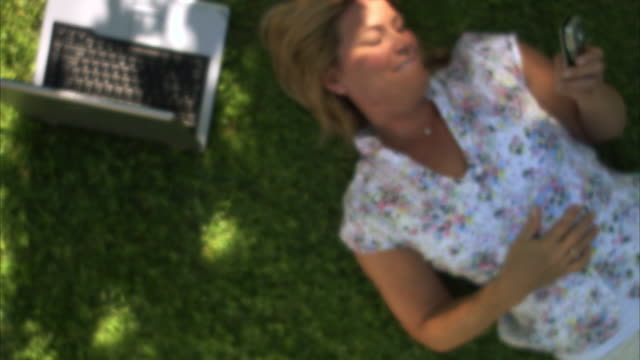 woman lying on a lawn with a laptop next to him reading an sms sweden. - one mature woman only stock videos & royalty-free footage