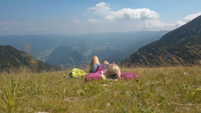 stockvideo's en b-roll-footage met slo mo vrouw die op een bergheuvel ligt - julian alps