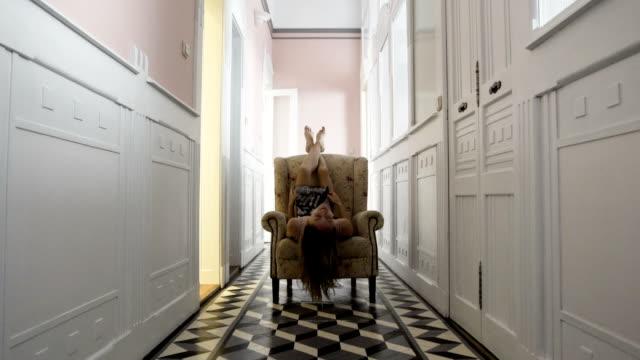 Woman lying on an armchair wearing satin dress, Seductive pose