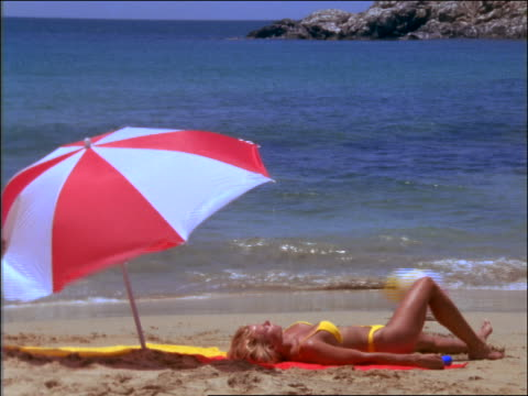 woman lying on beach / man with ball runs by / wind blows umbrella away / margarita is., venezuela - beach umbrella stock videos and b-roll footage