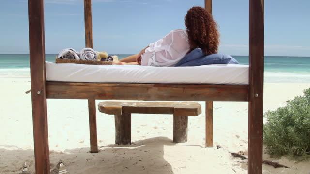 vídeos de stock, filmes e b-roll de woman lying on bed on sandy beach - tulum méxico
