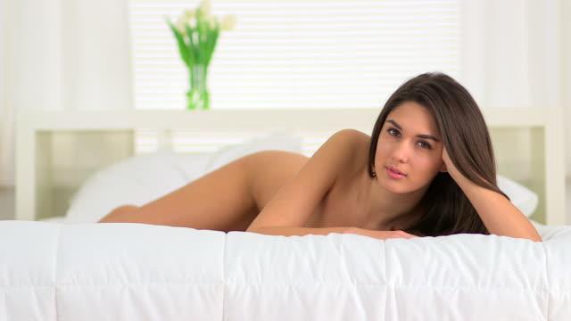 vídeos de stock, filmes e b-roll de woman lying on bed - reclinando