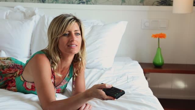 stockvideo's en b-roll-footage met ms woman lying on bed watching tv / golf de son termes, bunyola, mallorca, baleares, spain - zappen