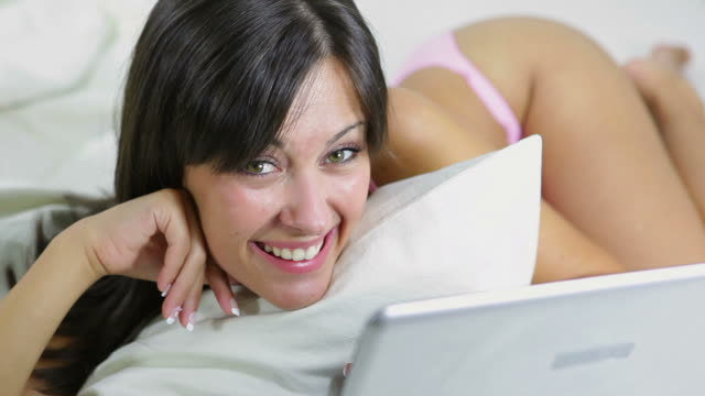 stockvideo's en b-roll-footage met woman lying on bed with laptop - dubbel bed