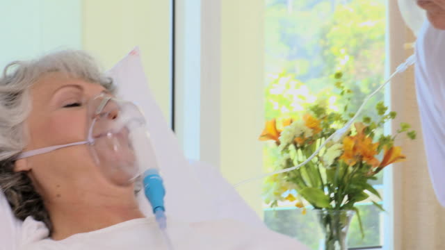 CU PAN Woman lying on bed with oxygen mask in hospital room / Cape Town, Western Cape, South Africa