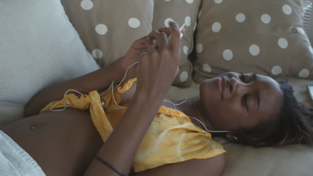 cu woman lying on couch, wearing earphones, nodding head to music, atlantic shores, bridgetown, barbados - mp3プレイヤー点の映像素材/bロール
