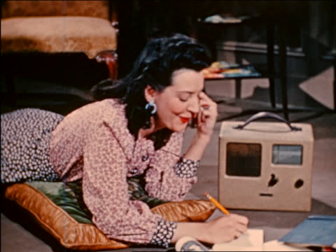 1941 woman lying on floor listening to radio + writing / industrial