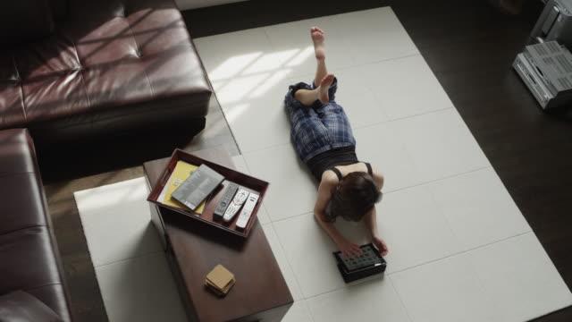 WS HA Woman lying on floor using tablet pc / Salt Lake City, Utah, USA