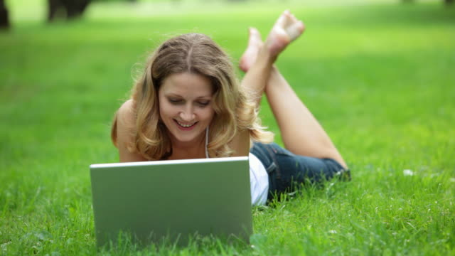 Woman lying on grass and using laptop