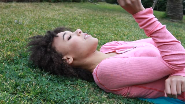 vidéos et rushes de woman lying on grass holding a clover - origine ethnique