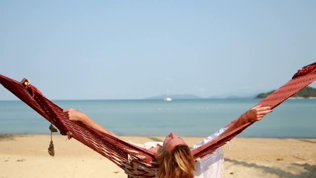 Woman lying on hammock on tropical beach