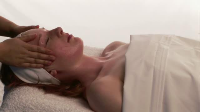 cu woman lying on her back & getting a massage / kinsale, ireland - 人の首点の映像素材/bロール