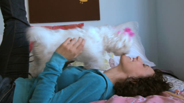 woman lying on her bed while her white dog licks her face