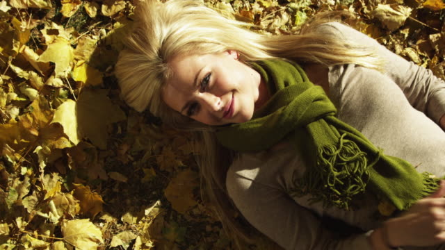 cu woman lying on leaves making hand gesture / provo, utah, usa - provo stock videos & royalty-free footage