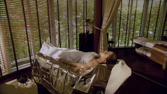 ws woman lying on massage table covered with foil / hua hin, thailand - kurbehandlung stock-videos und b-roll-filmmaterial