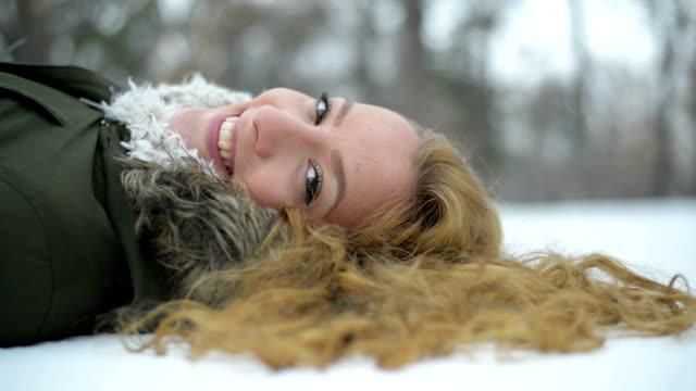 stockvideo's en b-roll-footage met vrouw liggend op sneeuw - natuurlijk haar