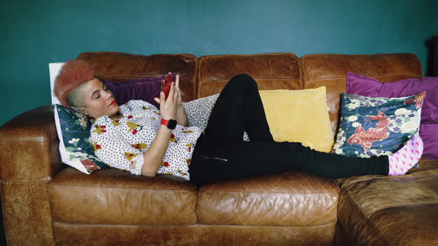 woman lying on sofa on mobile phone - lying on back stock videos & royalty-free footage