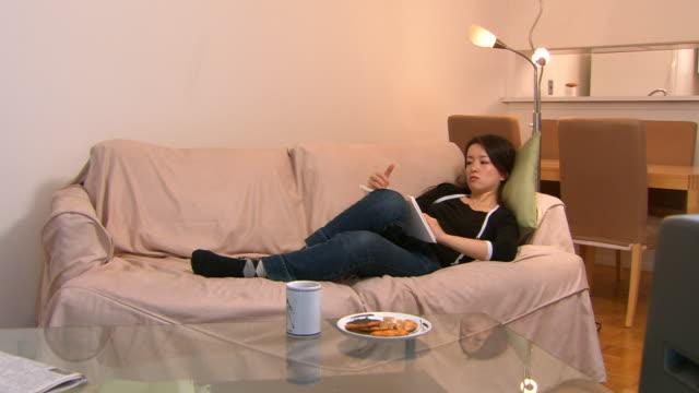 ms, woman lying on sofa, reading book - 怠惰点の映像素材/bロール