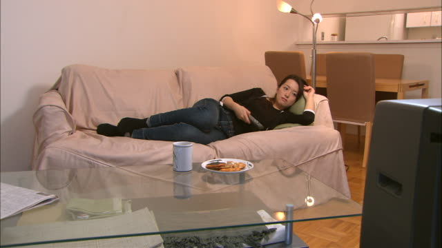 ms, woman lying on sofa, watching television - faulheit stock-videos und b-roll-filmmaterial