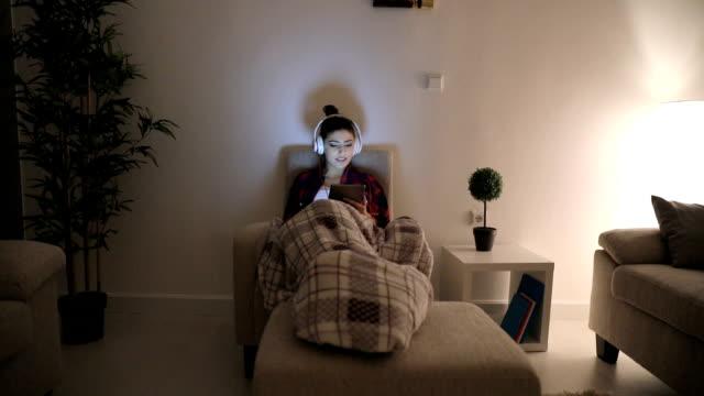vídeos y material grabado en eventos de stock de woman lying en el sillón y escuche música - manta ropa de cama