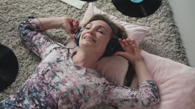 woman lying on the floor and listening to music via headphones - lying down stock videos & royalty-free footage
