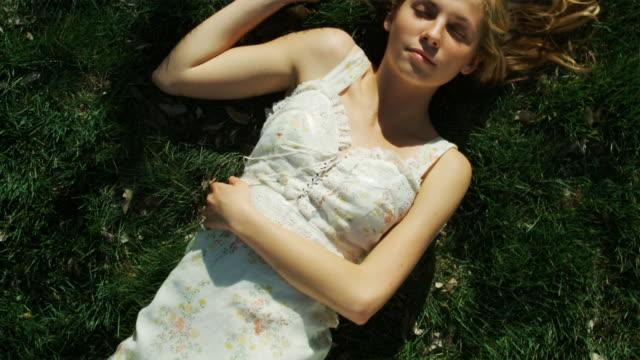 vídeos de stock e filmes b-roll de woman lying on the grass - só uma menina adolescente